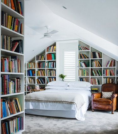 small attic library and bedroom with walls of bookshelves