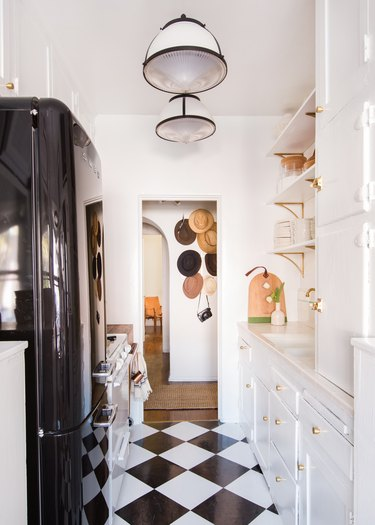 Black and white rental kitchen lighting idea with patterned flooring and white cabinets