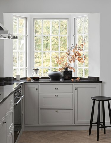 gray kitchen cabinet color with black countertops and white walls