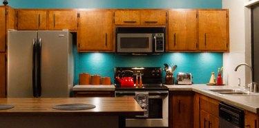 Retro wood cabinetry and teal backsplash