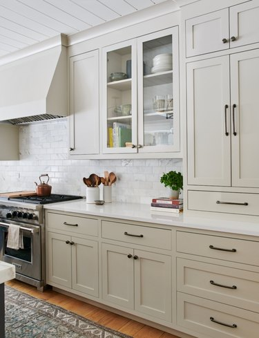 greige kitchen cabinet color with white countertops and white subway tile backsplash