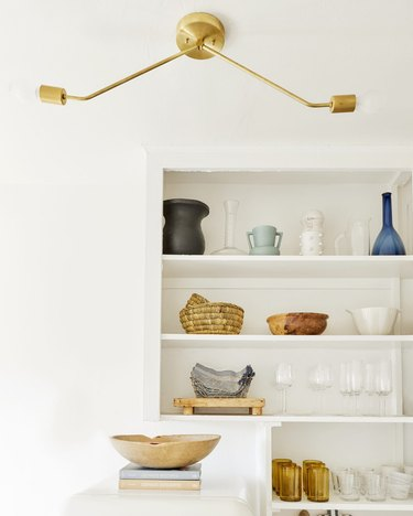 Modern rental kitchen lighting in white space with open shelving