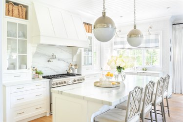white kitchen cabinet color with marble countertops and island