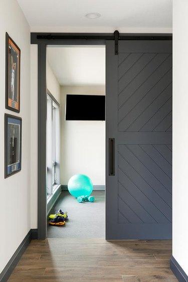 basement gym with sliding barn style door