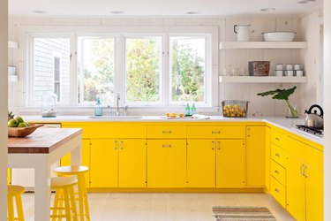 yellow kitchen cabinet color with white walls and countertops and a small island