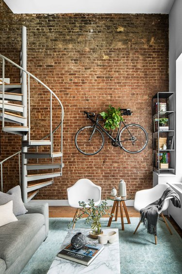 industrial style apartment living room with exposed brick wall and spiral staircase
