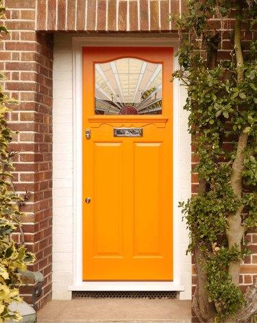 art deco stained glass in orange front door of brick exterior