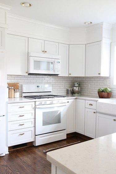 Recessed kitchen ceiling lights in all-white kitchen with wood flooring
