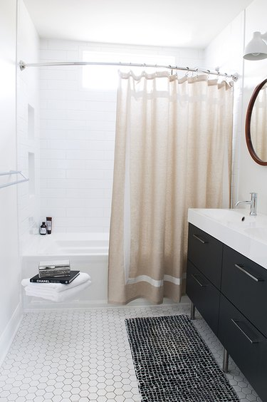 black-and-white bathroom idea with neutral shower curtain and tile flooring