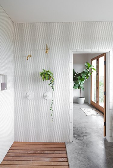 Hexagon mosaic wall tile in an open bathroom with concrete floors