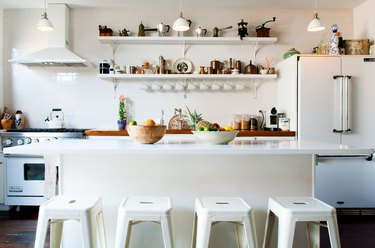 all-white kitchen with island and a set of open shelves