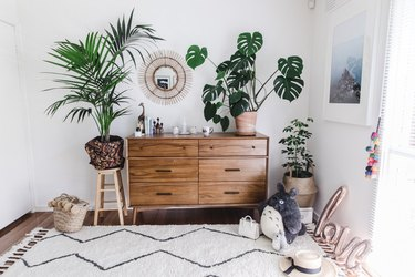 bohemian bedroom with plants and wood dresser