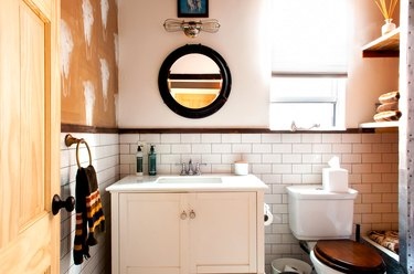 bathroom with small white vanity, undermount sink, round mirror with black trim, subway tile wall, built-in shelving, toilet with wood lid