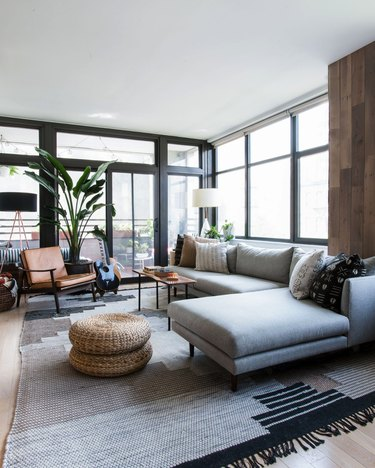 Living room layout idea with modern sectional sofa and woven floor poufs