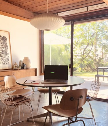 Modern dining room with laptop on table by Oonagh Ryan