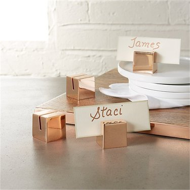"""cooper place holders with """"staci"""" and """"james"""" near stack of white plates"""