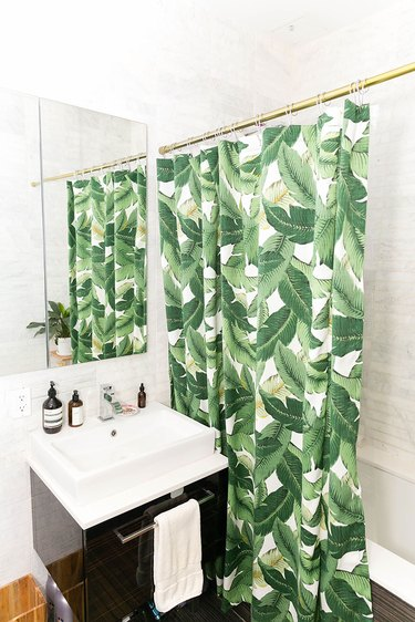 white bathroom with tropical foliage shower curtain