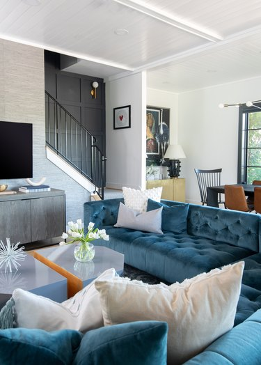 Living room layout idea with tufted sectional sofa in blue velvet