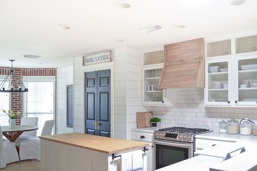 Exposed brick in the corner of a shiplap kitchen