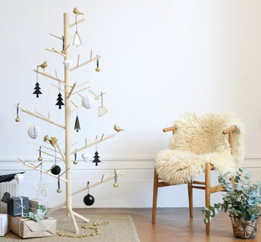 wood christmas tree with gifts and wishbone chair with sheepskin