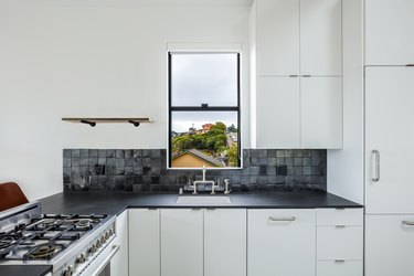 black kitchen backsplash with square glazed tile in white kitchen with black countertops