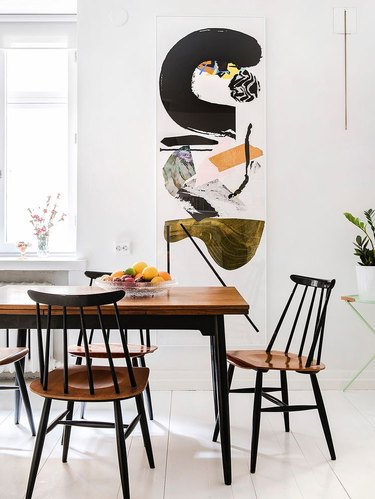 white Scandinavian dining room with wall art as focal point