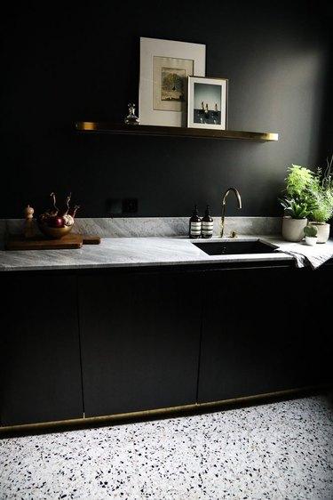 black kitchen with marble countertops and terrazzo floor