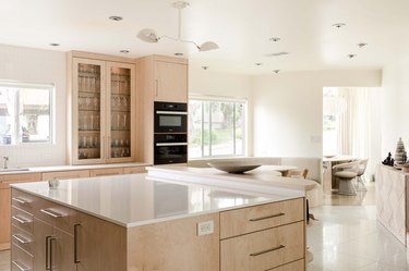 kitchen with light wood kitchen cabinetry, white stone countertops