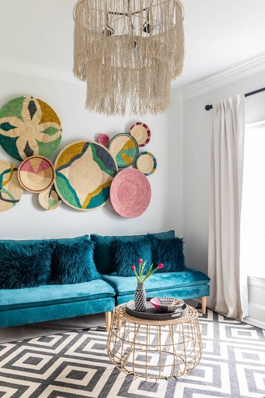 maximalist living room with blue sofa and basket wall hangings