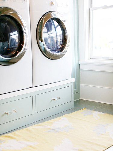 washer and dryer on pedestal with drawer storage in laundry room