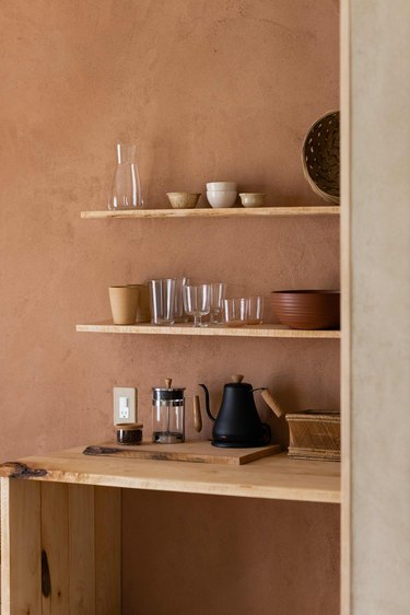 Pottery in shelves coordinates with hand-plastered walls.
