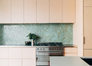 green kitchen backsplash with oak cabinetry and stainless steel appliances