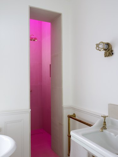 neon hot pink skylight in shower and vintage brass details in Harriet Anstruther's bathroom