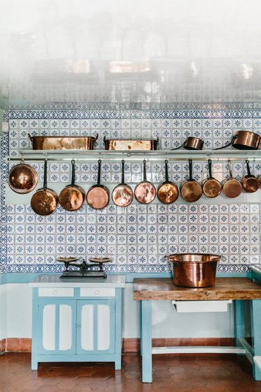 farmhouse kitchen backsplash with vintage tile and copper pans