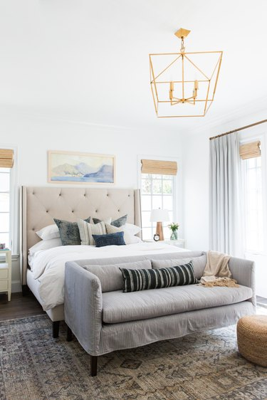 Bedroom layout idea with settee and tufted headboard with hanging pendant at ceiling