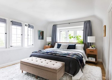 Bedroom layout idea with drapery at windows and bed bench in front of bed