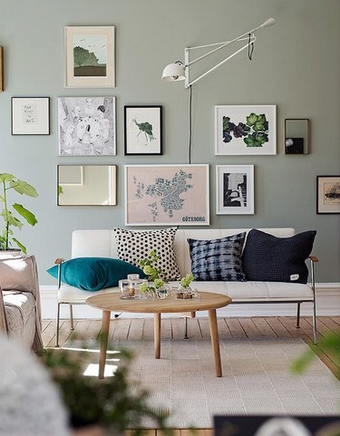 living room with sage green walls and gallery wall