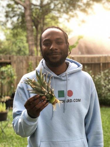 figure in backyard holding a pineapple top