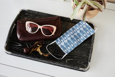 tray with sunglasses, keys, and face mask