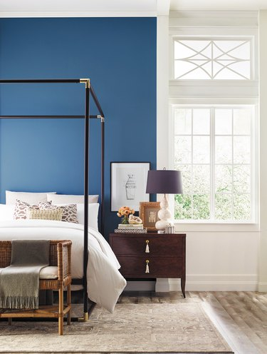 bedroom with black bed frame and blue wall