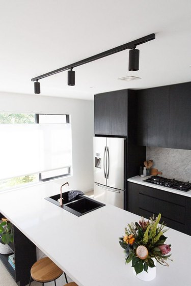 kitchen island sink with black cabinets and white countertops