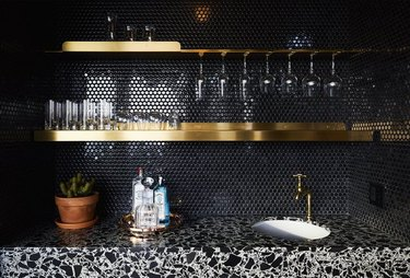 black penny tile mosaic with brass open shelving and terrazzo countertop