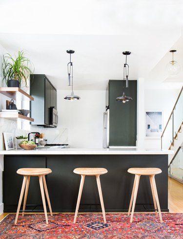 Modern bohemian kitchen lighting with black cabinets and pendants over counter