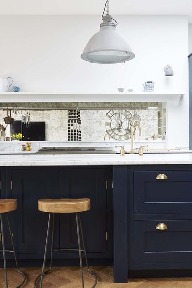 mirror kitchen backsplash with white countertops and blue cabinets