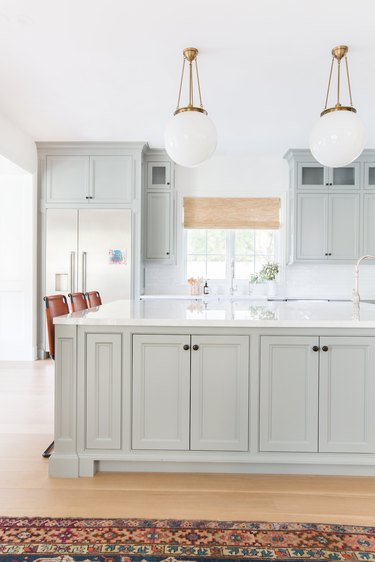 Gray kitchen island storage with cabinets and marble countertop