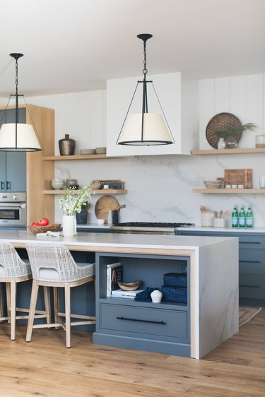 Blue kitchen island storage with marble waterfall countertop