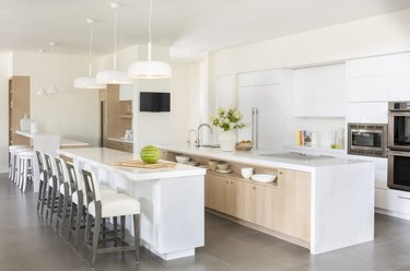 Long kitchen island storage with wood cabinets and marble waterfall countertop