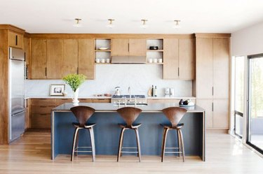 light wood kitchen cabinets with blue island and white countertops