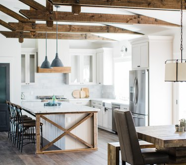 Farmhouse kitchen island idea with exposed ceiling beams and white cabinets with white countertops