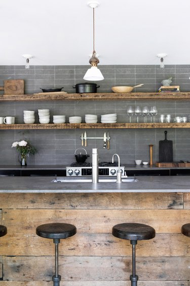 Industrial kitchen island idea with gray backsplash and gray countertops and open shelving